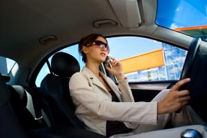 Junge Frau telefoniert mit dem Handy am Steuer eines Fahrzeugs